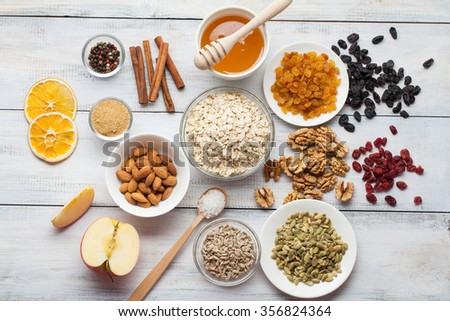 Grain free oat free paleo granola: mixed nuts, seeds, raisins, honey and coconut oil, white wooden background - stock photo