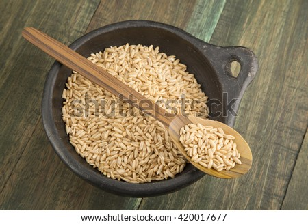 Grain oats in bowl and wooden spoon.
