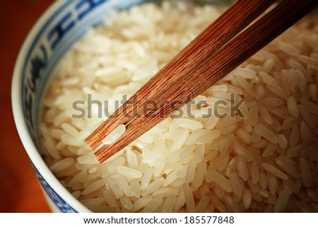 Grain of uncooked rice on chopsticks, selective focus - stock photo