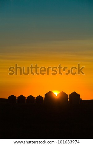 Grain Silos siloutted by sunset - stock photo