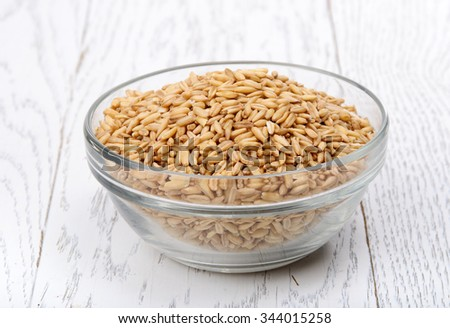 Grain wheat in glass bowl on wood table