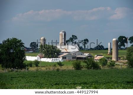 grain wheat metallic silo on cloudy sky background with farm - stock photo