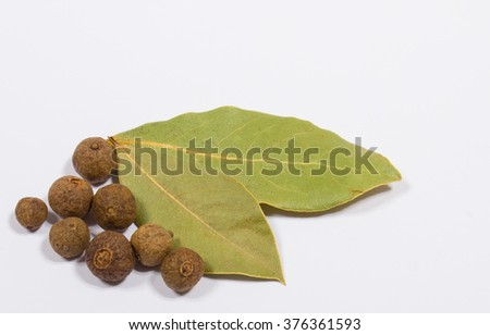 Grains of allspice and bay leaf isolated on white background
