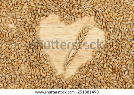 Grains of barley on a wooden board with a heart shaped space with an ear of barley - stock photo