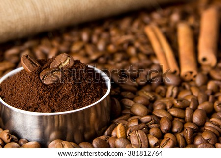 Grains of black coffee, ground coffee and cinnamon on a background of sacking