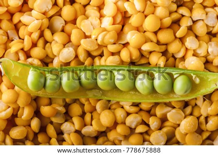 Grains of fresh ripe green peas in a pod on a background of crushed peas