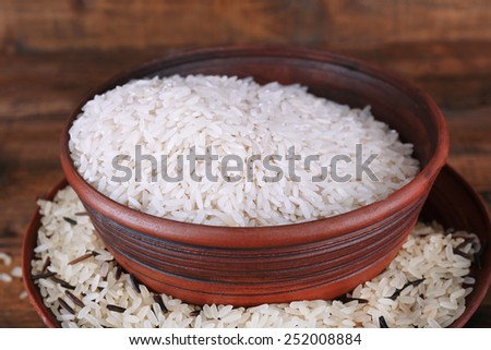 Grains of rice in bowls on wooden background