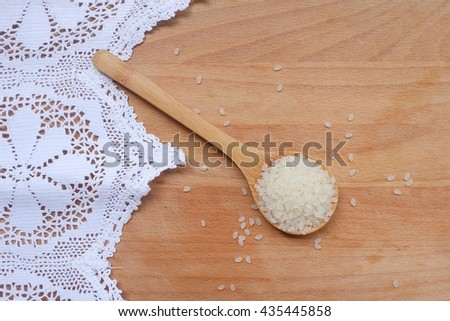 Grains of white rice in wooden spoon on kitchen table background. Close up Top view. - stock photo
