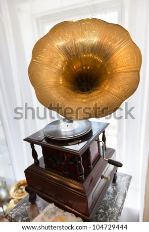 Gramophone in front of a window in vintage interior - stock photo