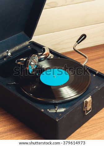 Gramophone with a vinyl record on wooden table