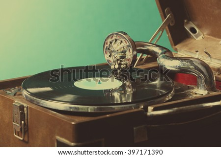 Gramophone with vinyl record on table on wall background - stock photo