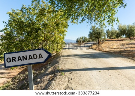 Granada road sign by side of dry dusty road with olive trees and mountains in the distance - stock photo