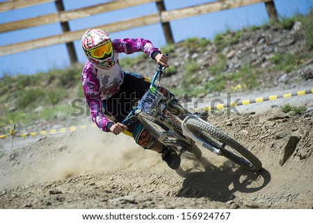 "GRANADA, SPAIN - JUNE 30: Unknown racer on the competition of the mountain downhill bike ""Bull bikes Cup DH 2013, Sierra Nevada "" on June 30, 2013 in Granada, Spain"
