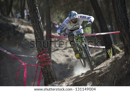 """GRANADA, SPAIN - OCTOBER 25: Unknown racer on the competition of the mountain downhill bike """"Cumbres Verdes, La Zubia"""" on October 25, 2012 in Granada, Spain - stock photo"""