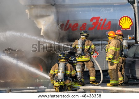GRANBY, QC, CANADA - MARCH 10: Firemen fighting a fire on tank trucks at a gas station March 10, 2010 in Granby, QC, Canada.