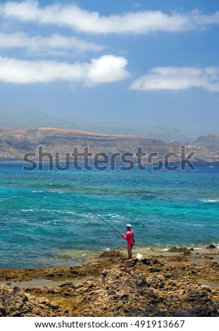 GRAND CANARY, SPAIN-MAY. 15: A sole man is seen fishing on rocky coastline of  Playa Las Cantera Las Palmas Grand Canary Island Spain on May 15, 2015.