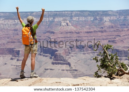 Grand Canyon hiking woman hiker happy and cheerful with arms raised up outstretched in joy. Winner and success concept with excited elated female hiker outdoors in Grand Canyon, Arizona, USA. - stock photo