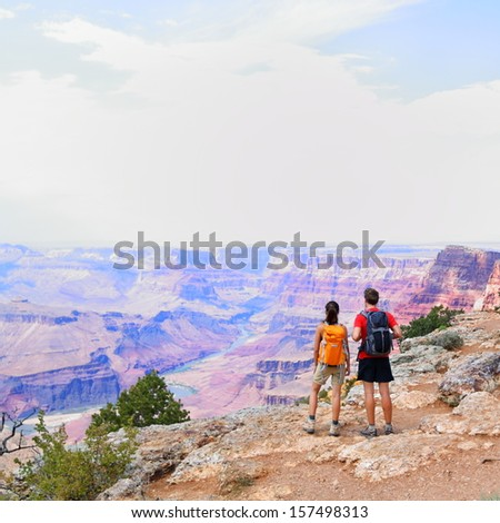 Grand Canyon - people hiking looking at view. Hiker couple walking on South Rim trail of Grand Canyon, Arizona, USA. Beautiful american landscape.