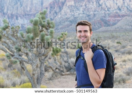 Grand Canyon travel - happy man mountain hiker with backpack on the rocky dry mountains