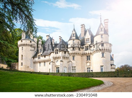 Grand castle in France, Europe. Beautiful chateau of white stone with towers and sharp-cornered roof with green lawn and path in foreground and blue cloudy sky in background. Architecture of Europe. - stock photo