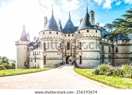 Grand castle in France, Europe. Chateau of white stone with towers surrounded with green lawns and trees. Road leading to entrance in foreground, blue cloudy sky in background. Architecture of Europe.