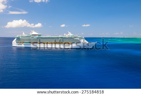 """GRAND CAYMAN, CAYMAN ISLANDS - APRIL 3, 2008: """"Freedom of the Seas"""" giant cruise ship was tendered next to the shore. Over 4,000 guests went out to visit tropical island. - stock photo"""