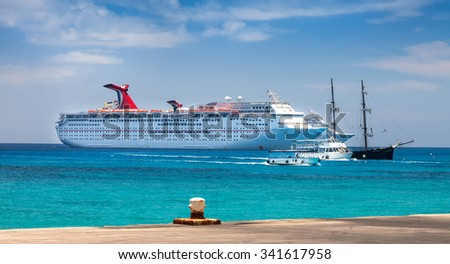 GRAND CAYMAN, CAYMAN ISLANDS - JULY 13, 2011:  Ships in the harbor of Grand Cayman.  Visitors are transported to the main island by water taxi's and ferries from the cruise ships in port for the day.
