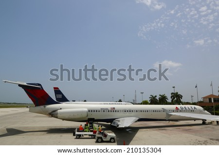 GRAND CAYMAN, CAYMAN ISLANDS - June 13  Delta Airlines McDonnell Douglas MD-80 and US Airways jet at Owen Roberts International Airport at Grand Cayman on June 13, 2014 - stock photo