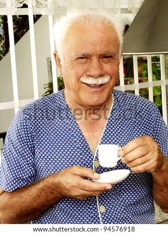 Grand father drinking coffee in a kitchen. - stock photo