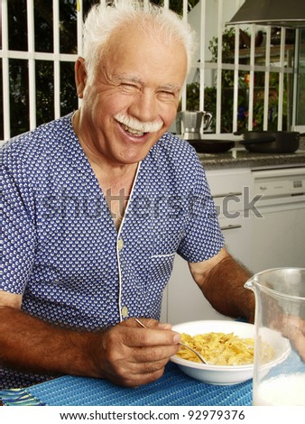Grand father having breakfast at kitchen,Grand father eating cereal corns flakes. - stock photo