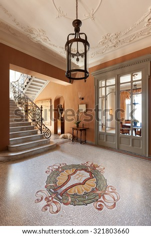 Grand foyer with mosaic floor in luxury mansion