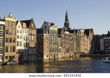 Grand historical buildings and the tower of the Old Church along the Damrak canal in the evening sun in Amsterdam, Holland