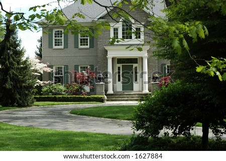 Grand house with green shutters, white pillars and curved driveway