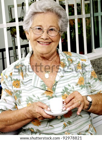 Grand mother drinking coffee in a kitchen. - stock photo