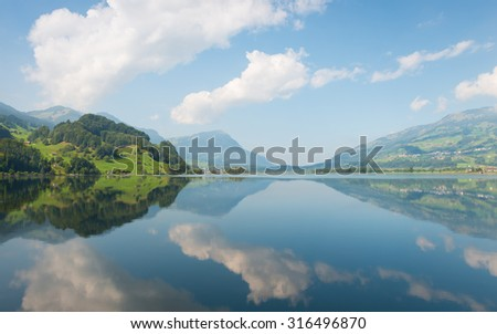 Grand panorama of mountain lake. Clouds and nature are reflected in a mirror surface. - stock photo
