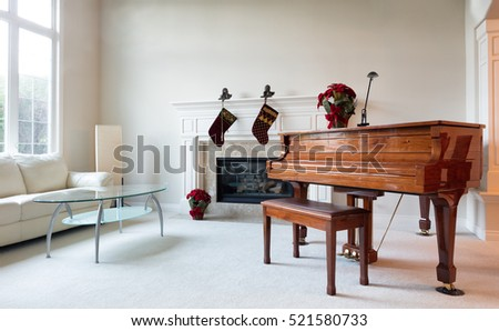 Grand piano surrounded by Christmas objects during with bright daylight coming through the living room window.