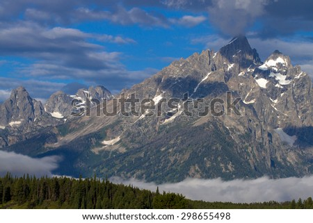 Grand Teton Mountain with glaciers and fog above the Snake River - stock photo