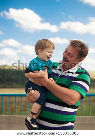 Grandchild and grandfather having fun outdoors in summer
