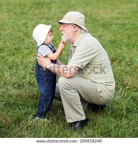 Grandchild pulling his grandfathers beard - stock photo