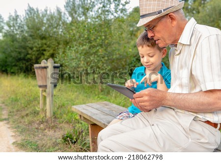 Grandchild teaching to his grandfather to use a electronic tablet on a park bench. Focus on grandfather. Generation values concept. - stock photo