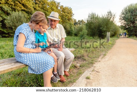 Grandchild teaching to his grandparents to use a electronic tablet on a park bench. Generation values concept. - stock photo