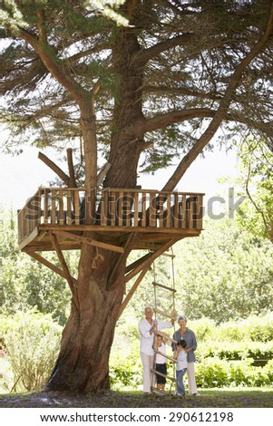 Grandchildren And Grandparents Standing By Tree House In Garden - stock photo