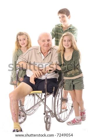 Grandchildren with Grandfather in wheelchair - stock photo