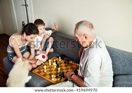 grandchildren with grandpa playing chess horizontal - stock photo