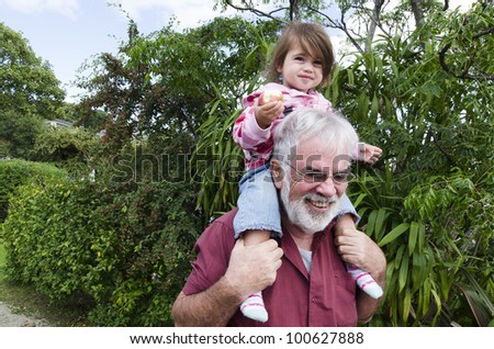 Granddad carry his grandchild on his shoulder.Concept photo of grandparents, grandfather, grandad,granddad ,grandchild, childhood, granddaughter, relationship, lifestyle,family, education. - stock photo