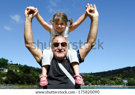 Granddad carry his grandchild on his shoulder during summer vacation. - stock photo