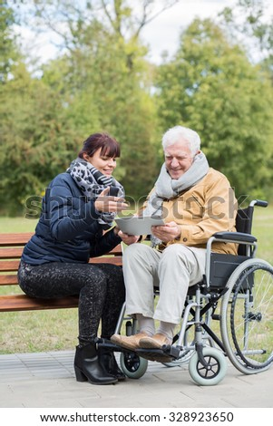 Granddaughter and disabled senior man with tablet - stock photo