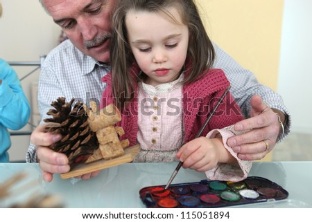 Granddaughter and grandfather painting - stock photo