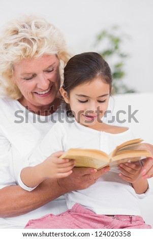 Granddaughter and grandmother reading a novel together on the sofa - stock photo