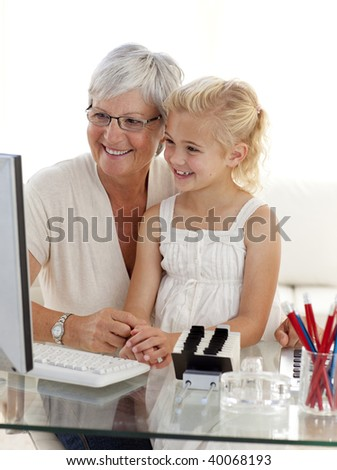 Granddaughter and grandmother using a computer at home - stock photo